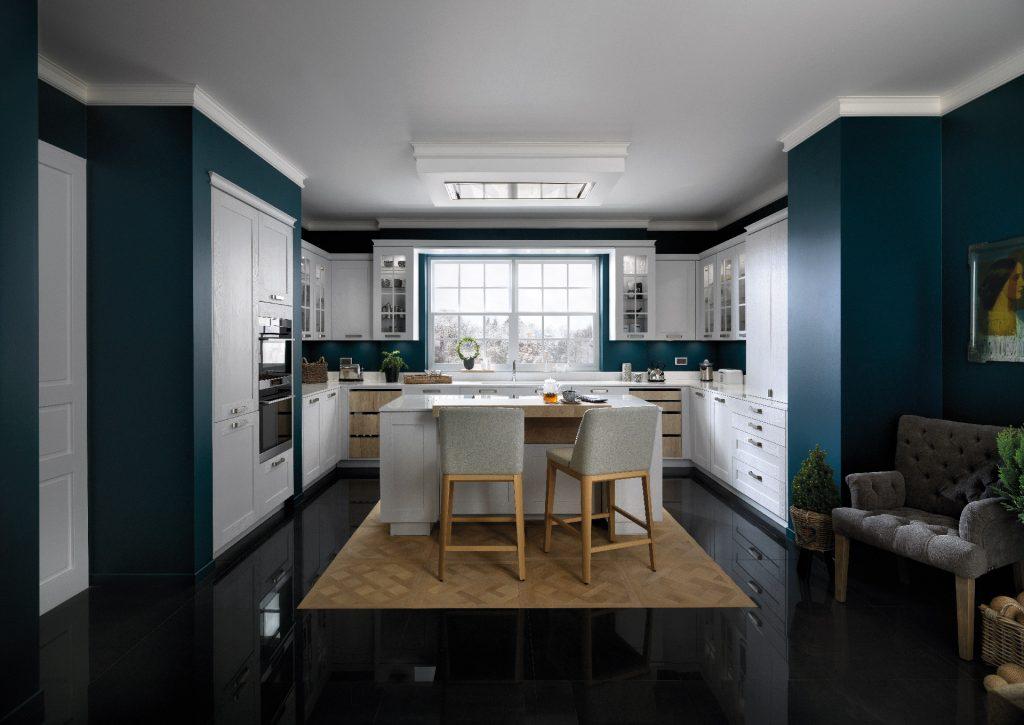 Vue d'ensemble de la cuisine Nebraska, coloris gris clair Celest, avec un îlot central, façades blanches et Buffet-Déco couleur bois.