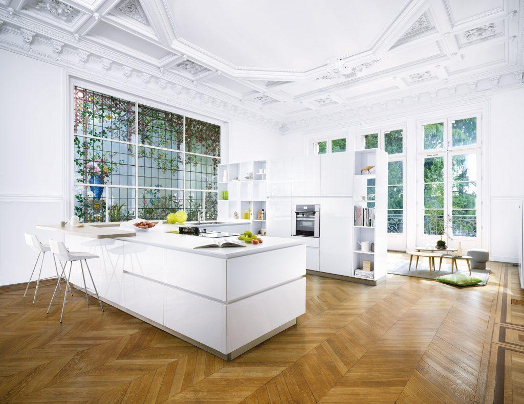Vue d'ensemble de la cuisine Strass Eolis, coloris blanc neige brillant Everest, avec un plan snack découpé non linéaire et le salon derrière la bibliothèque.