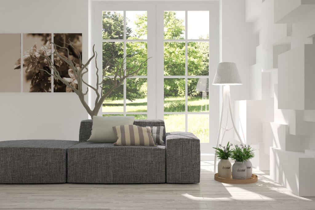 Vue d'un canapé gris posé devant une fenêtre montrant un jardin, avec un lampadaire blanc et des plantes vertes.