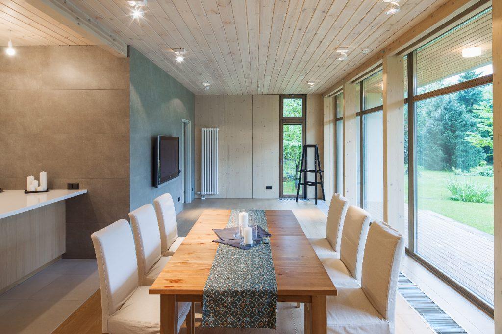 Une salle à manger avec une table en bois sur laquelle est posé un chemin de table en tissu à motifs et avec 6 chaises recouvertes de tissu blanc, de grandes baies vitrées montrant le jardin sur le côté.