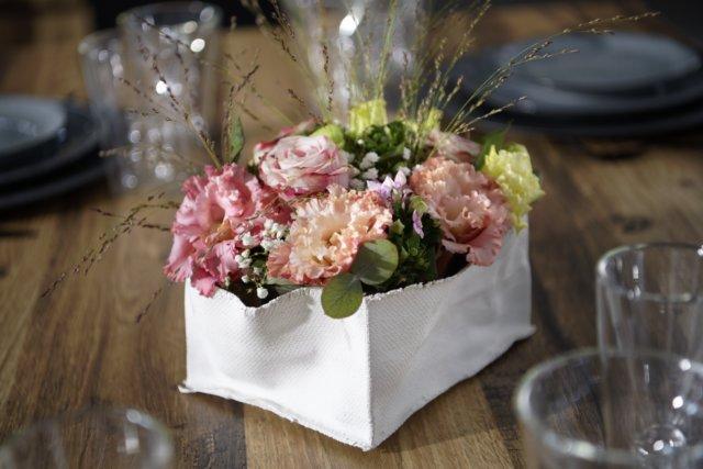 Centre de table composé de fleurs blanches et roses avec des feuilles vertes dans un panier en tissu blanc posé sur une table en bois.