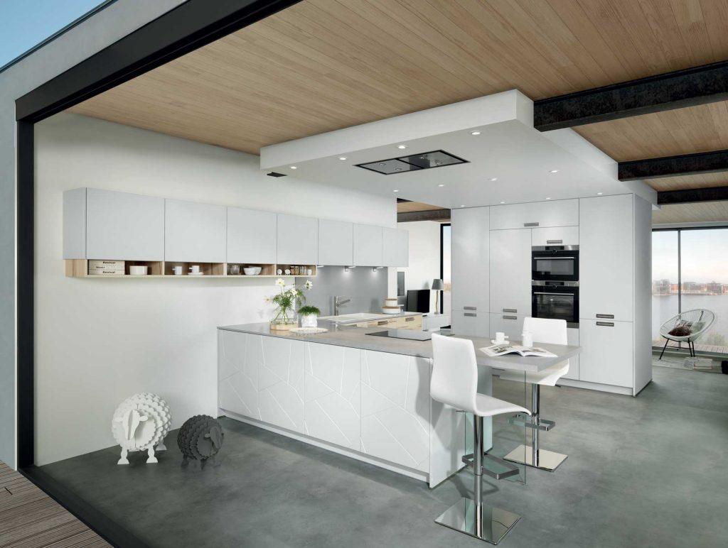 Vue d'ensemble de biais d'une cuisine Arcos coloris bois clair Ikori et Lazer coloris gris clair Celest avec le plan bar et les tabourets avec le pied carré au premier plan et le mur d'armoires en arrière plan.