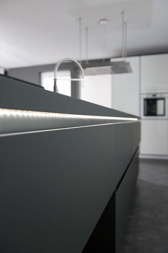 Vue en perspective du rail LED sous le plan de travail dans la cuisine Glamour Vertica en blanc neige Snow White et le modèle Arcos Edition en noir Nano Black.