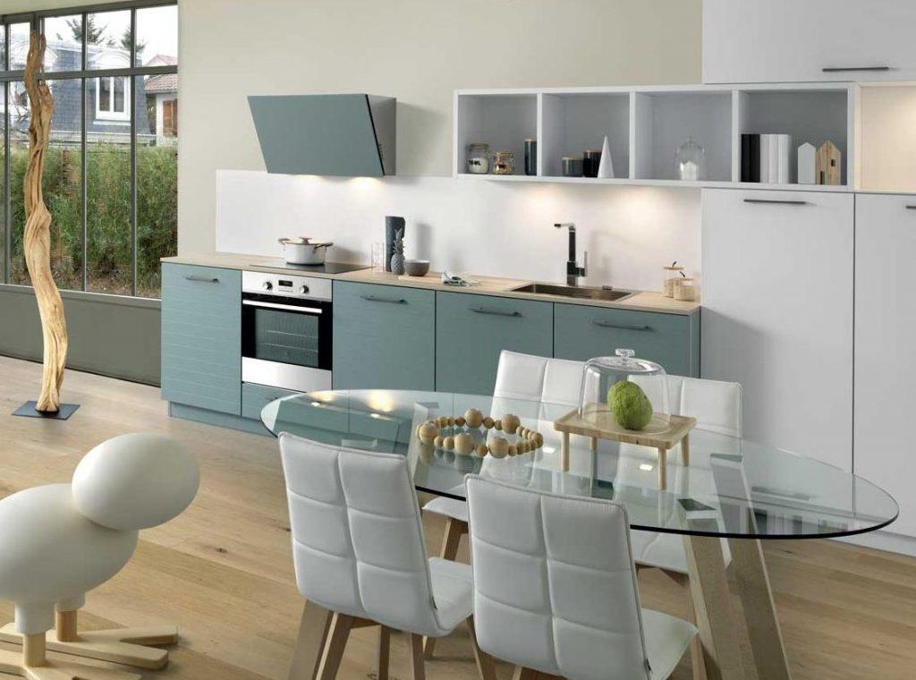 Vue d'ensemble de biais d'une cuisine Multiway coloris vert clair grisé Green Tea et Arcos en blanc, avec une table en verre et des chaises blanches au premier plan.