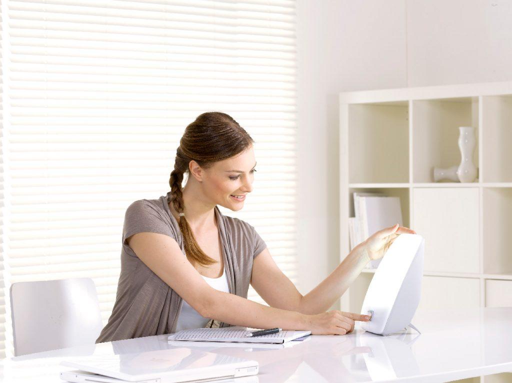 Une femme assise à un bureau blanc active un appareil de luminothérapie.