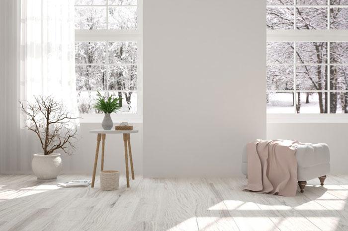 Vue d'un salon avec un pouf en tissu posé devant une fenêtre et d'une table d'appoint posée devant une autre fenêtre montrant un paysage hivernal.