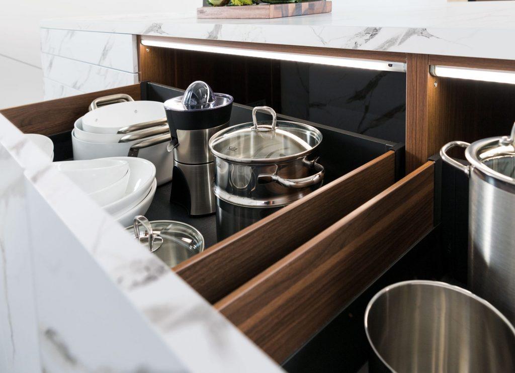 Vue des blocs coulissants de meubles bas avec vaisselle mise en situation et éclairage intérieur, façade en gris Marmor.