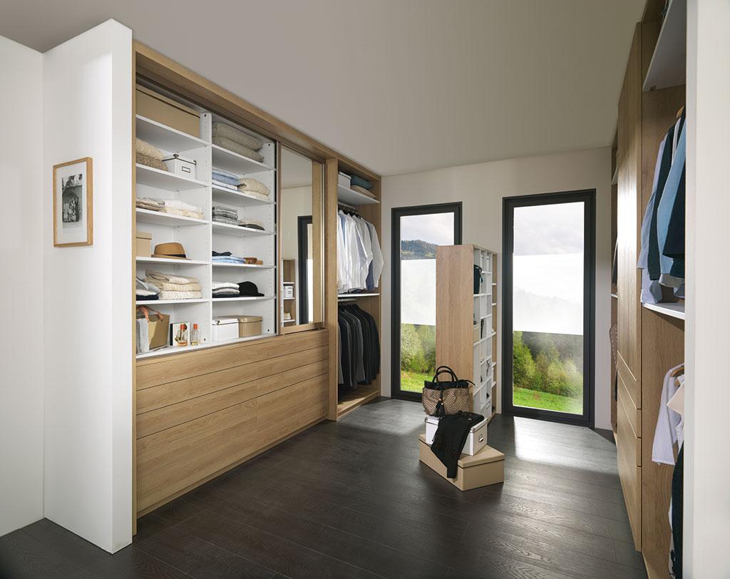 Vue de biais d'un dressing avec la porte coulissante miroir du côté gauche du placard et au milieu, une étagère ouverte des deux côtés.
