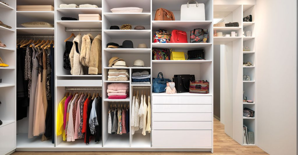 Vue de l'intérieur d'un dressing : compartiments de rangement, étagères, penderies courtes, porte-pantalons, tiroirs coulissants, bloc coulissant et étagères pour sacs à main.