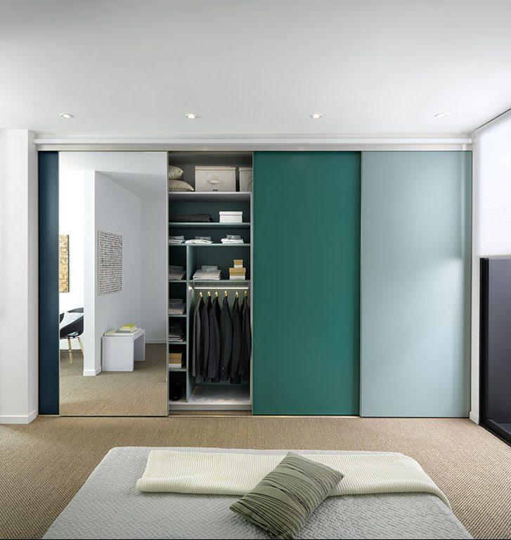 Vue de face d'un dressing modulable avec 3 portes coulissantes en deux tonalités de vert et 1 porte coulissante miroir.
