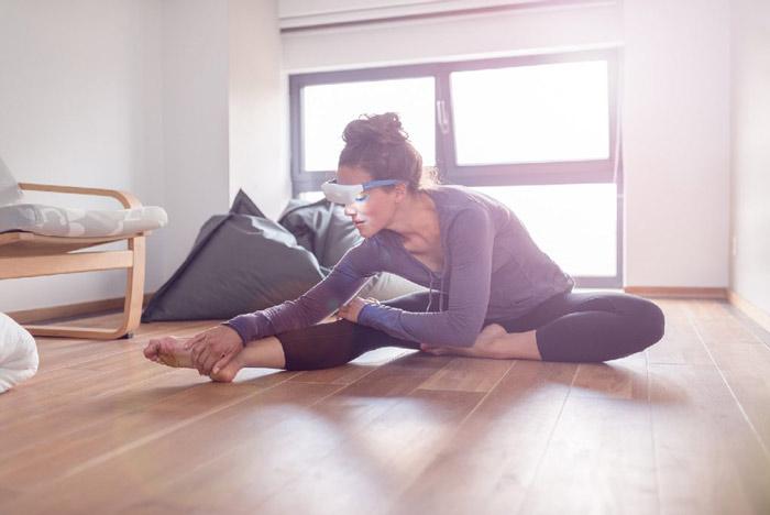 Une femme habillée en tenu de yoga et avec des lunettes de luminothérapie, fait du stretching dans un salon bien illuminé.