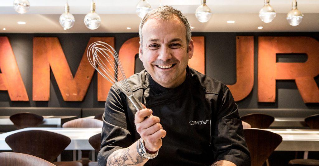 Portrait de Carl Marletti, chef pâtissier parisien, avec un fouet de cuisine.