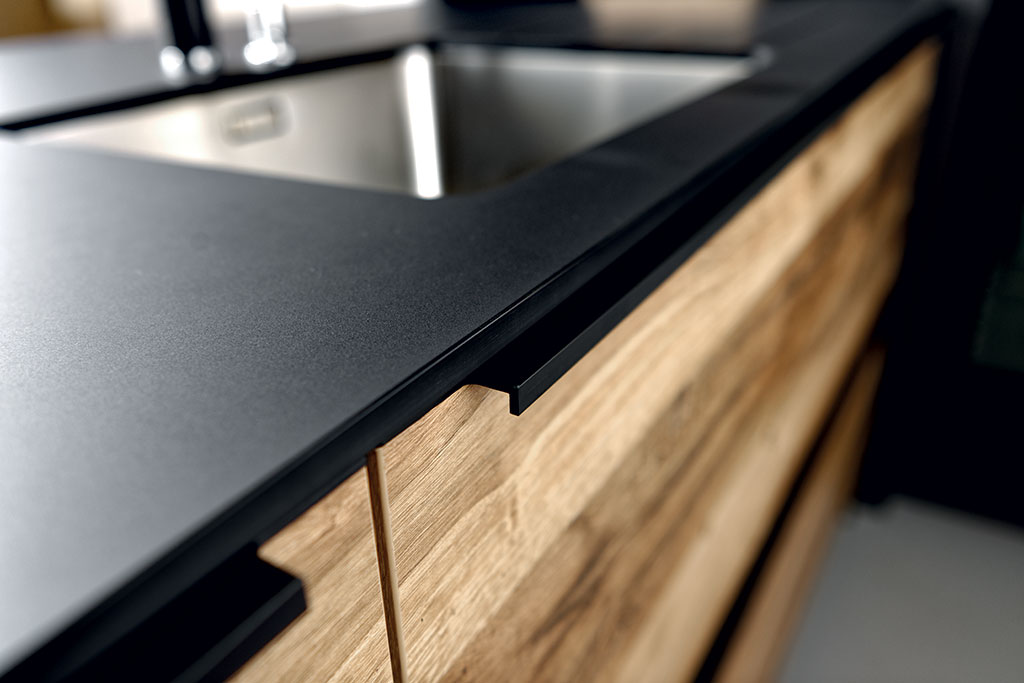 Zoom du chant du plan de travail stratifié Compact noir de la cuisine Arcos Edition, ambiance Wild Black.