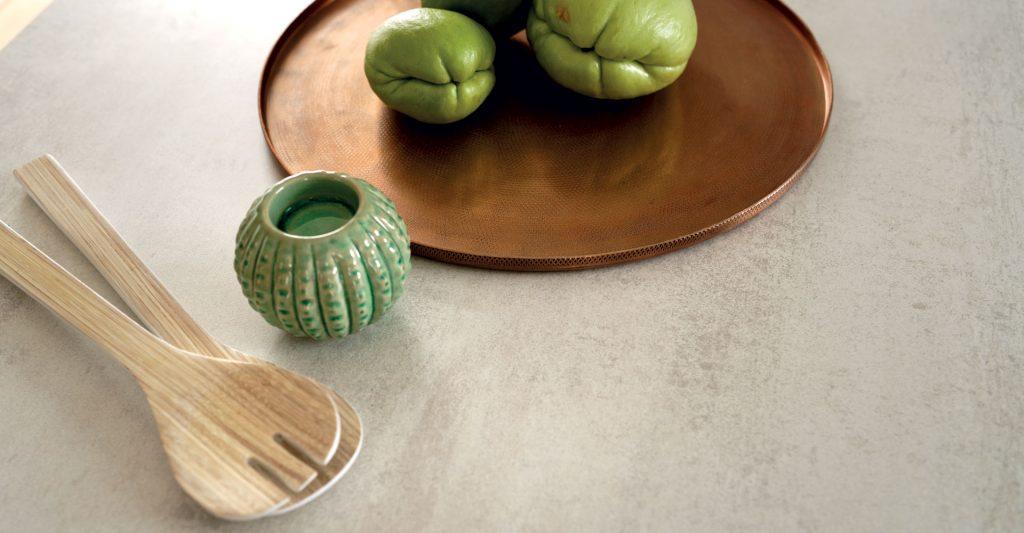 Vue de dessus d'un plan de travail beige et mise en situation avec cuillères à salade en bois et un plateau de légumes.