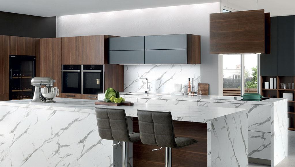 Vue zoomée de la cuisine Arcos Edition, composée d'un îlot central avec deux tabourets, les meubles en effet bois marron foncé et noir et le plan de travail effet marbre.