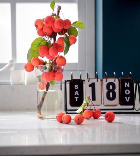 Une branche de mini pommes dans un vase transparent à côté d'un calendrier posés sur un plan de travail en quartz blanc.