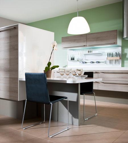 Vue d'une cuisine en bois clair avec des meubles éclairés.