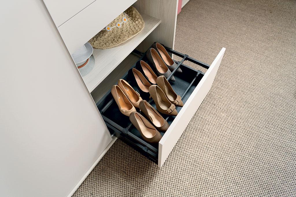 Vue de biais d'un bloc à chaussures blanc avec quelques paires de chaussures à talons rangés.