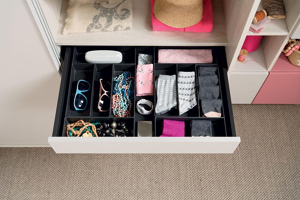 Vue de l'intérieur d'un tiroir ouvert organisé avec des boîtes de rangement dans le dressing Arcos coloris gris clair effet bois et Loft coloris rose et vert clair grisé.
