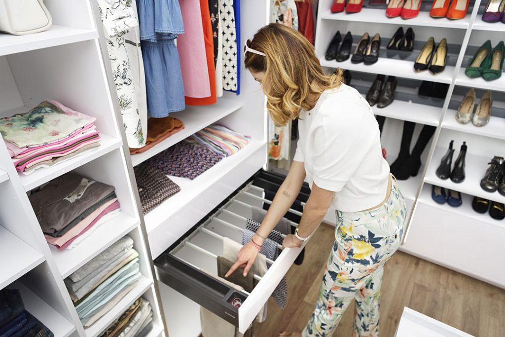 Une femme cherche un pantalon dans le porte-pantalons de son dressing sur mesure coloris blanc neige.
