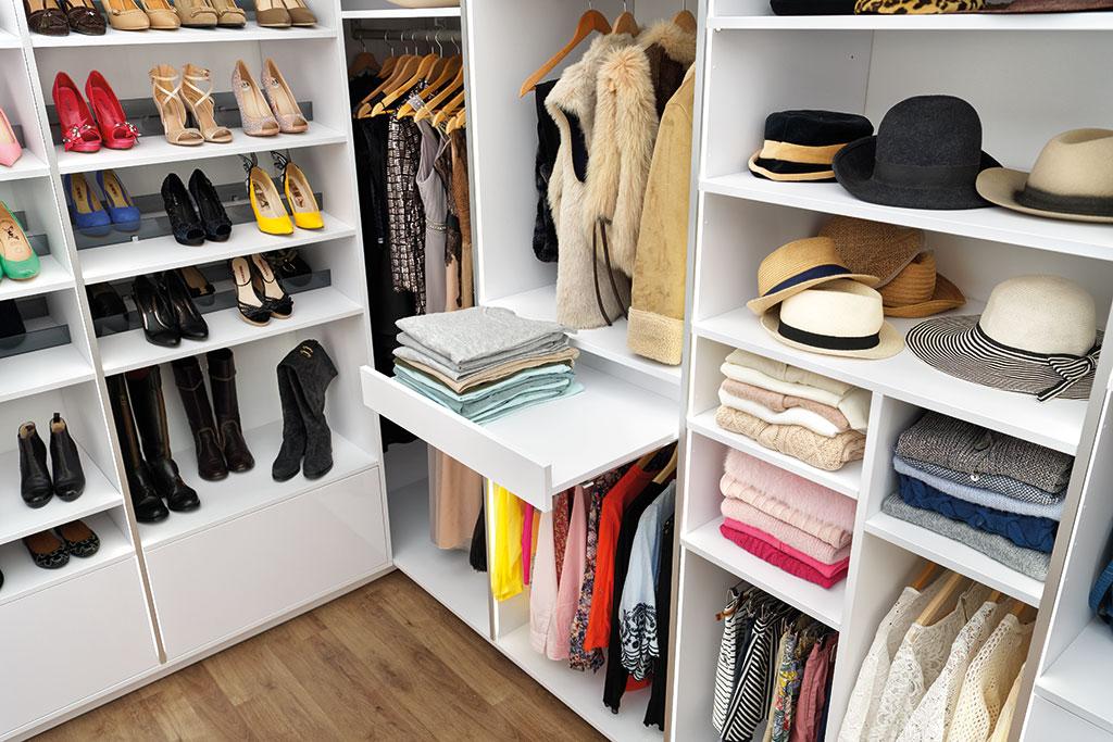 Vue sur l'angle du dressing blanc Showroom Privé, avec des étagères, de la penderie et du rangement pour les chaussures et les chapeaux.