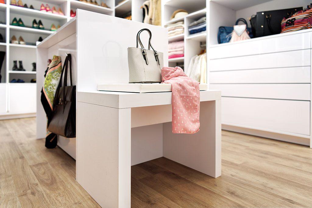 Vue de biais qui présente un banc blanc et un meuble de rangement qui sépare la pièce dressing.