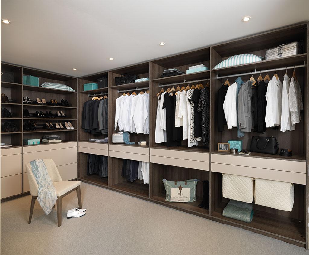 Vue de l'intérieur d'un dressing coloris bois et beige avec les bacs à linge au premier plan et les range-chaussures au fond.