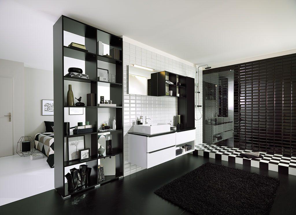 Vue d'ensemble de la salle de bains en noir et blanc avec la chambre en arrière plan et le meuble de rangement niches ouvertes et fermées au premier plan.