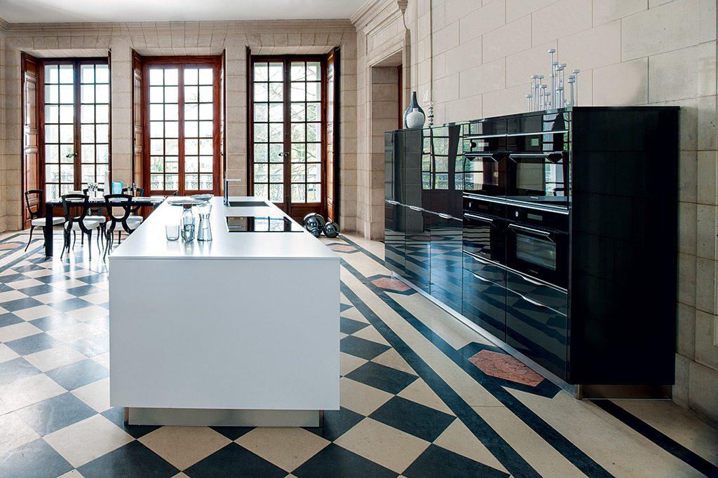 Vue de coté de la cuisine sur mesure Contraste Eclatant avec l'îlot central blanc et des meubles noirs.