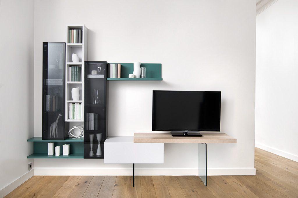Vue de face du meuble TV avec la composition mise en situation, avec des étagères verticales blanche et noires avec le verre fumé et des étagères horizontales vertes.