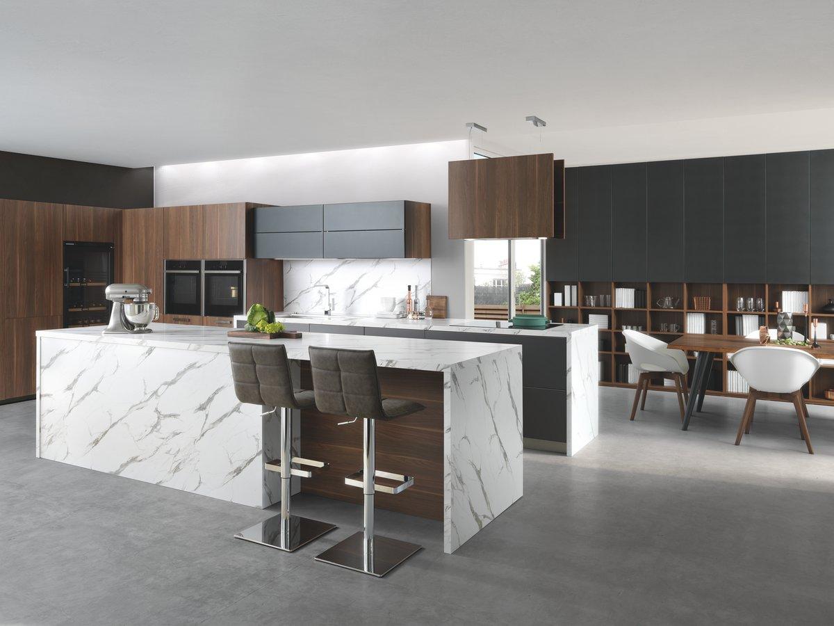 Vue en biais d'une cuisine composée d'un îlot central au premier plan, une table et des chaises à droite et le buffet en arrière plan, coloris gris clair marbré et marron.