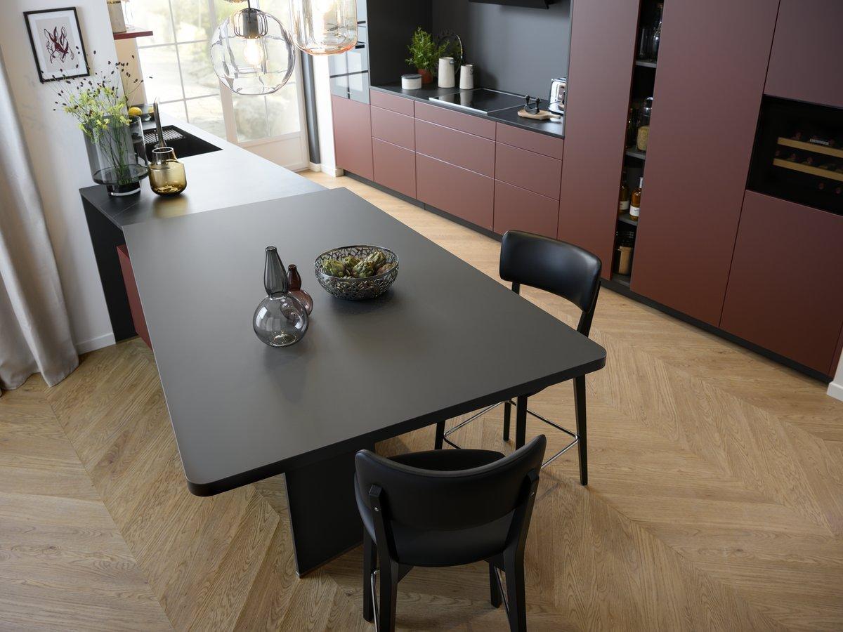Vue sur ilôt central d'une cuisine ouverte en coloris rouge sombre