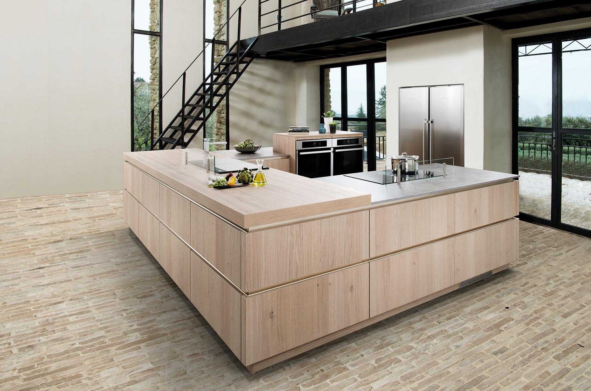 Vue d'ensemble en biais de la cuisine Major Eolis avec le plan de travail en bois clair, réfrigérateur 2 portes, plaque de cuisson, four...