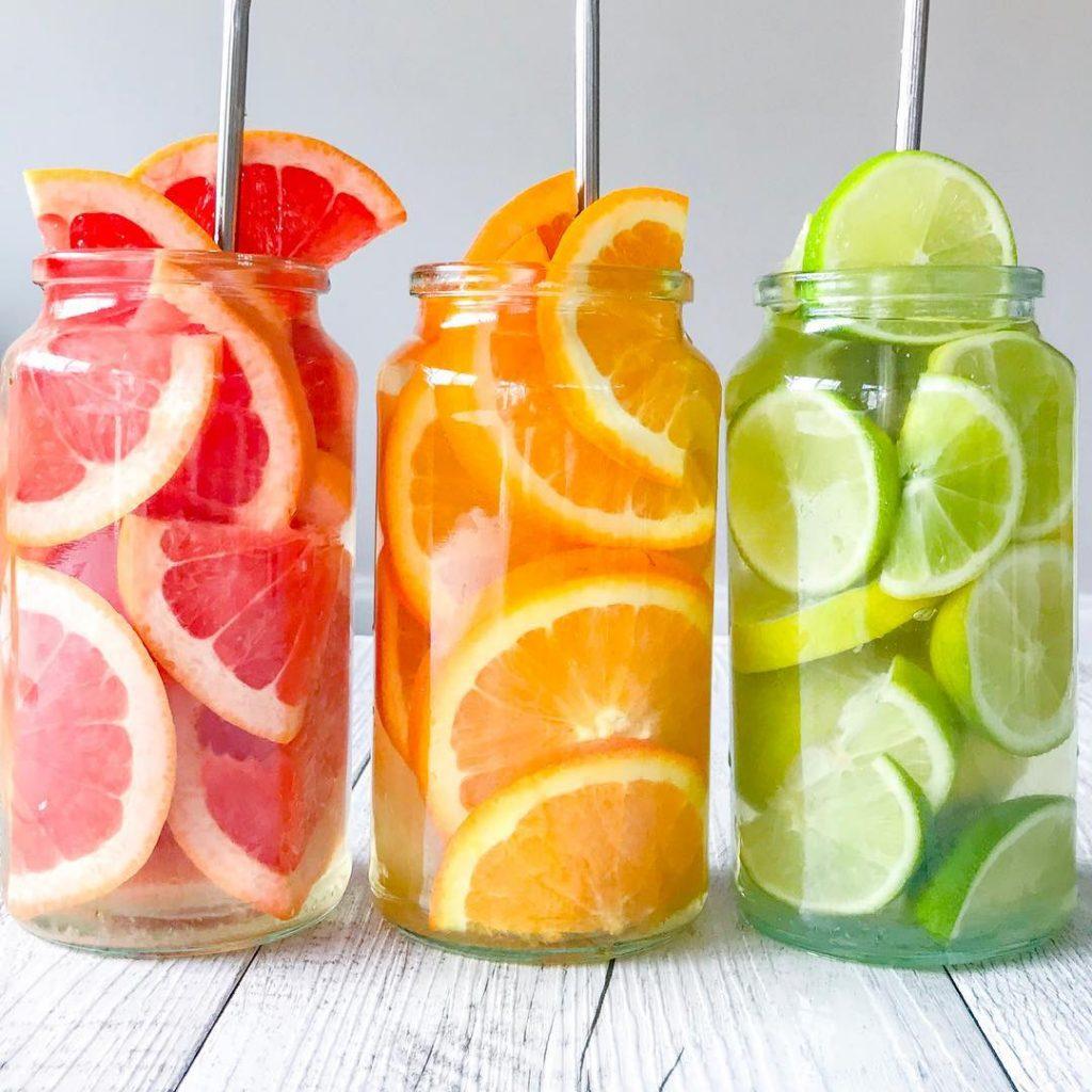 Trois bocaux avec l'eau aromatisée aux agrumes : pamplemousse, orange et citron vert.