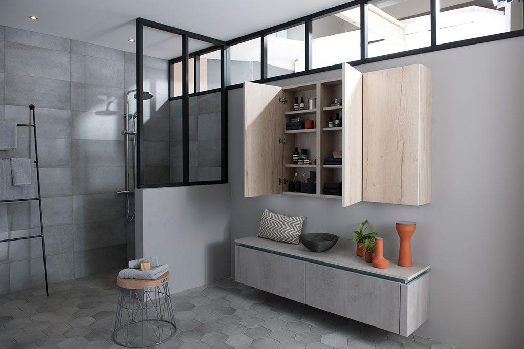 Salle de bains avec une douche italienne style industriel et deux meubles de rangemnet de salle de bains en coloris gris clair marbré et décor bois.