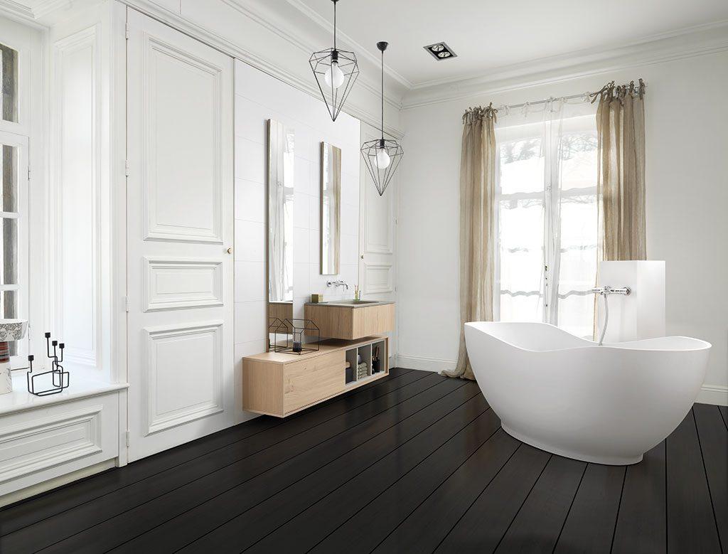Salle de bains avec baignoire, deux miroirs sur mesure, un meuble de rangement de salle de bains et un meuble sous vasque coloris bois teinté pastel.