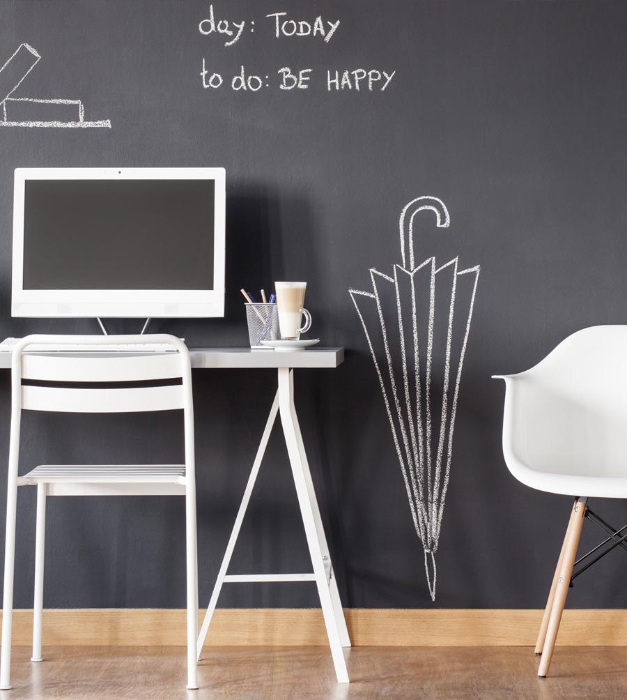 Espace bureau devant un mur noir avec dessins à la craie blanche