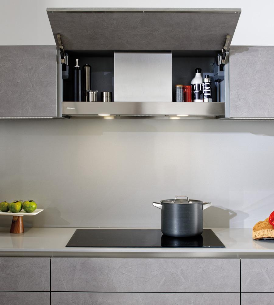 Vue du meuble haut avec la hotte cachée ouvert dans une cuisine grise.