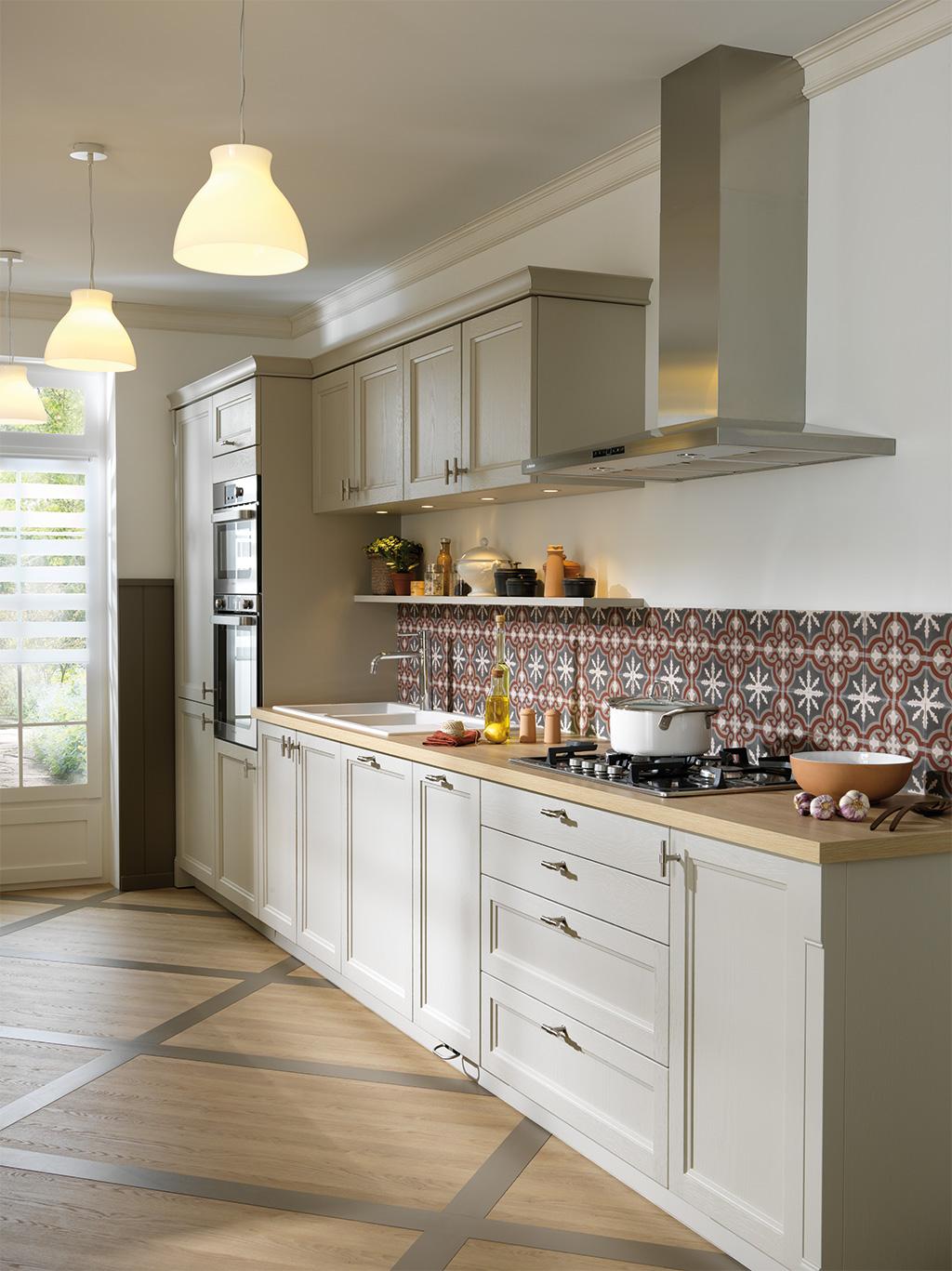 Cuisine en coloris grège clair et plan de travail en bois, avec une crédence avec des formes géométriques.