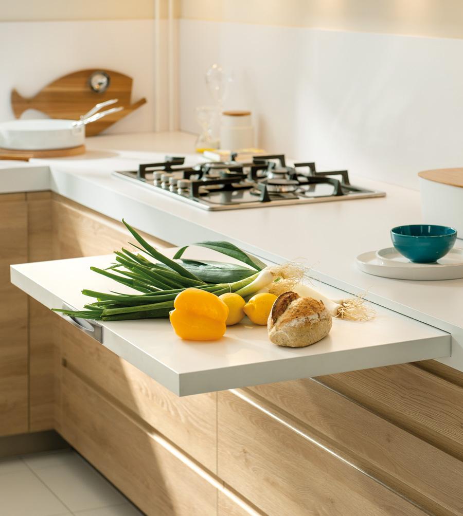 Plan de travail extensible blanc avec des fruits, des légumes et du pain posés sur lui.