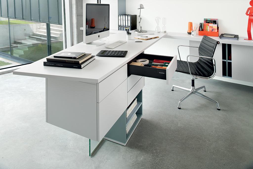 Bureau gris clair dans une pièce dédiée au télétravail, avec un chaise noire.