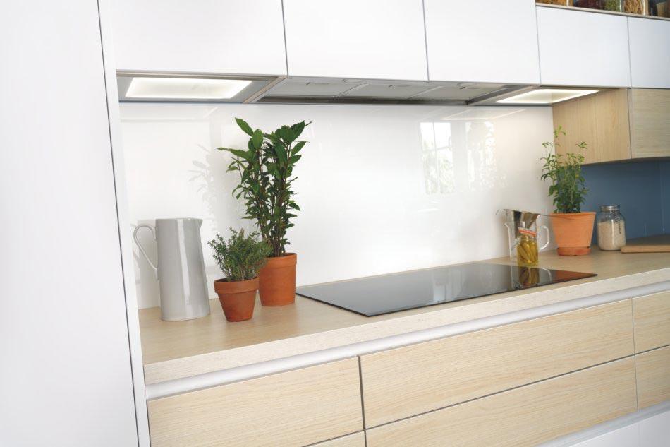 Crédence murale en verre blanc dans cuisine blanche et bois