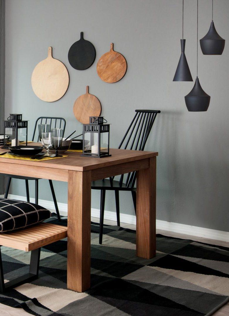 Les éléments design et cette table en bois massif sont sublimés par un mur gris vert.