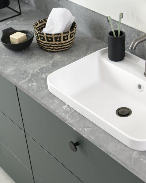 Ce plan de toilette est contrasté par le gris aspect pierre minérale et la délicatesse du vert mat.