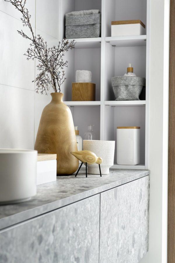 Le gris terrazzo de cette salle de bain est contrasté par de petits éléments en bois.