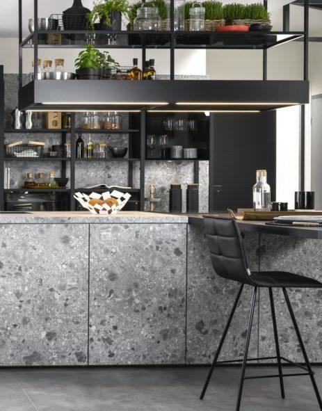 Les structures métalliques noires s'accordent également avec l'ilot central en gris terrazzo.