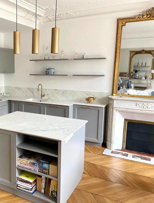 L'effet or vieilli sur le miroir et les suspensions harmonise somptueusement cette cuisine grise et quartz blanc - Réalisation magasin Schmidt Barentin.