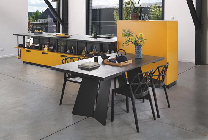 Vue d'ensemble de la cuisine ouverte sur l'espace repas avec chaises et tables en céramique