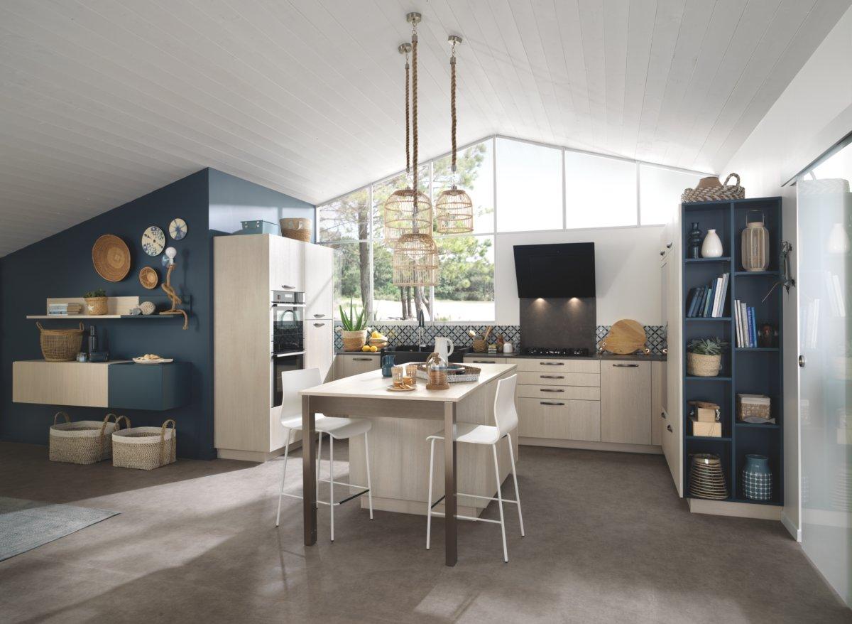 Vue d'ensemble en biais de la cuisine ouverte avec niches de rangement intégrées dans les meubles