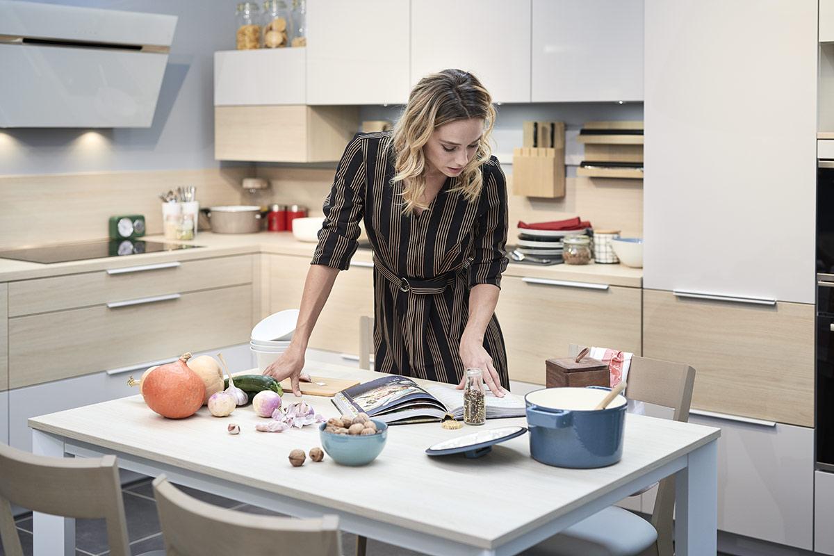 Femme qui prépare son plat en cuisine avec des légumes racines